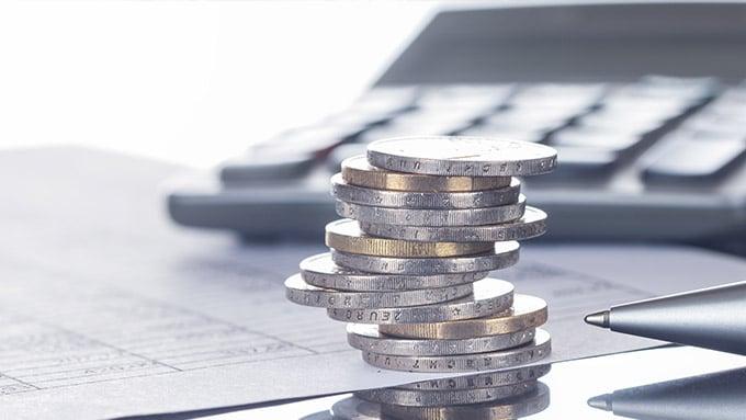 pile de pièces de monnaie avec stylo et calculatrice