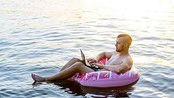 homme tenant un ordinateur portable sur une bouée