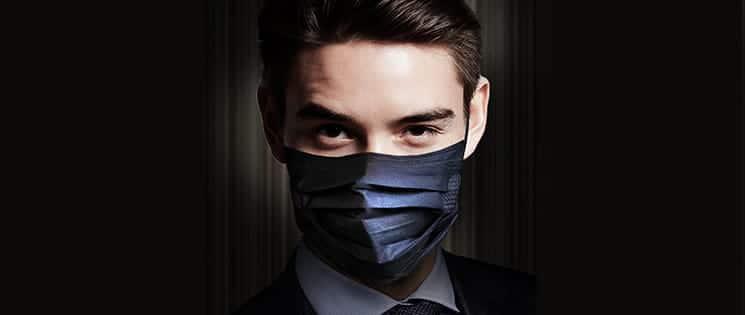 Plan serré visage Homme en costume sur fond noir. Il porte un masque de protection de couleur foncée contre les virus.