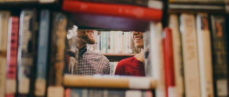 image d'une pile de livres formant un creux au milieu de l'image laissant voir le bas de visage d'un homme et d'une femme qui se sourient