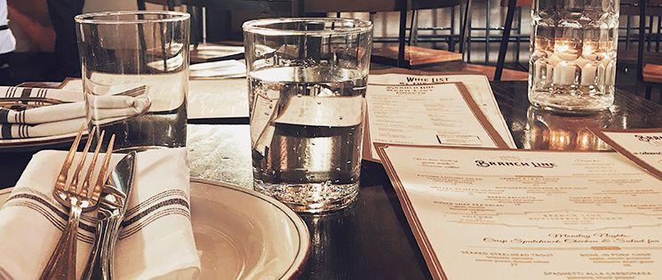 Table de restaurant avec un seul couvert et la carte des menus