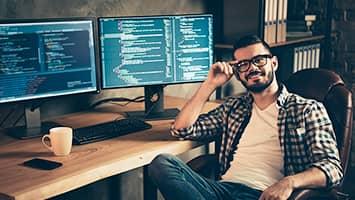 Homme barbu, chemise à carreaux devant deux écrans d'ordinateur