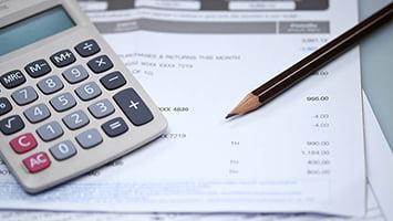Une calculatrice et un crayon en papier sont posés sur un bulletin de paie.