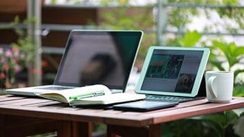 Un ordinateur portable et une tablette sont allumés posés sur une table en bois