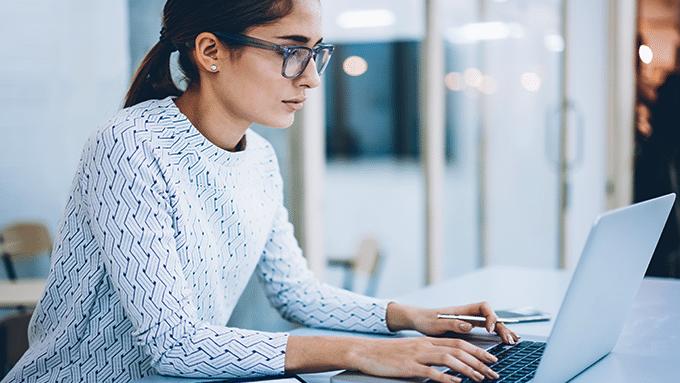 Une femme assise à son bureau à ses mains sur le clavier d'un ordinateur portable