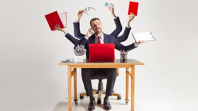 Un homme en costume est assis à son bureau. Il a six bras dont chaque main tient un objet de bureau différent.