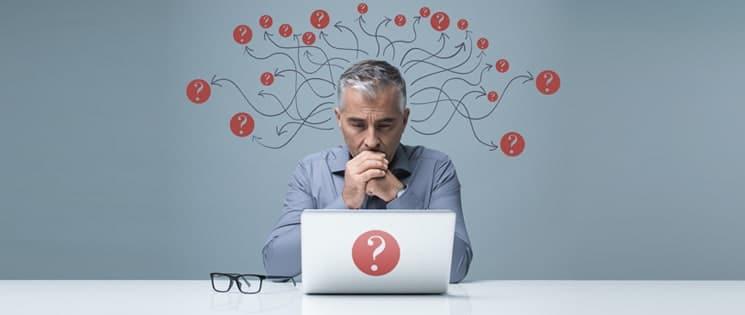 Sur un fond gris, un homme poings joints aux lèvres regardent l'écran de son ordinateur portable