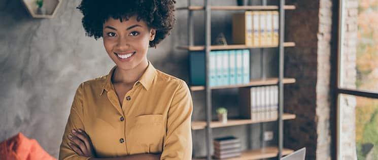Une femme, bras croisée, est devant son bureau de travail et derrière elle, se trouve un meuble de rangements pour des dossiers.