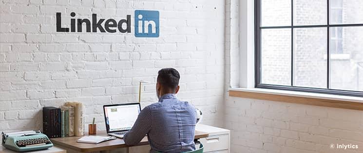 """À son bureau de travail, un homme assis face à son mur en brique blanc avec dessus l'inscription du logo """"Linkedin"""""""