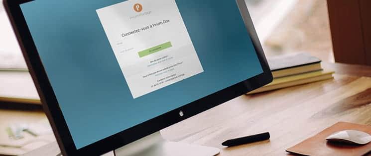 Un ordinateur sur une table de bureau affiche à l'écran la page de connexion de l'application Prium ONE.