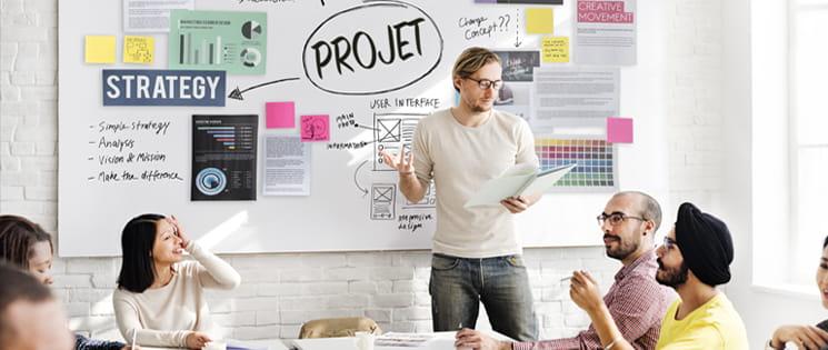 Des collaborateurs, hommes, femmes, autour d'une table face à un chef de projet.