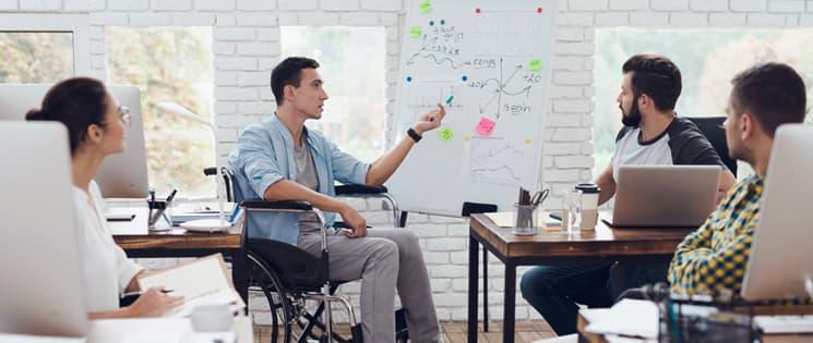 Un homme en chaise roulante présente un projet sur un whiteboard devant trois collaborateurs, deux hommes et une femme.