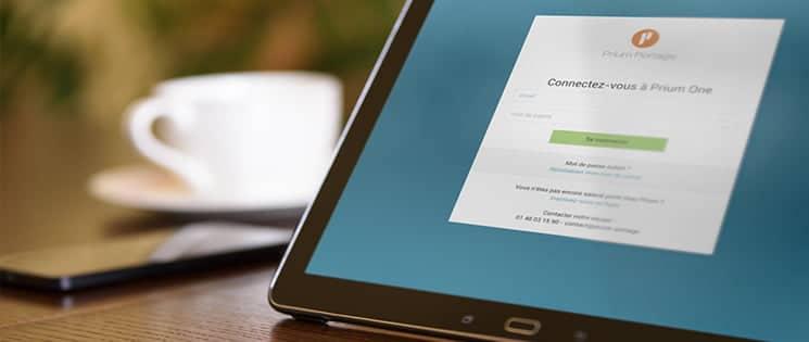 Une tablette affiche la page de connexion Prium One, à côté, une tasse à café et un smartphone