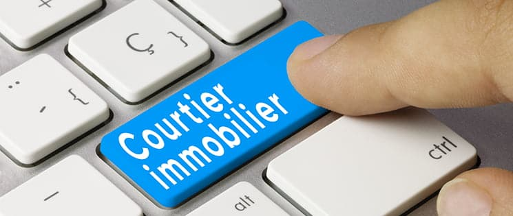 "Un index indique la touche bleu ""Courtier immobilier"" d'un clavier d'ordinateur"