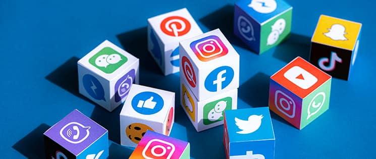 Sur fond bleu, un ensemble de dés dont chaque face représente un réseau social différent : Snapchat, Pinterest, Twitter, Facebook...