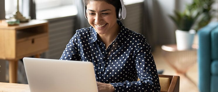 Une femme avec un casque audio sur la tête devant son ordinateur
