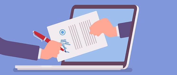 Le principe de la signature électronique imagé par une main tenant un contrat à signer qui sort de l'écran d'un ordinateur portable. Une autre main tient un stylo et signe le contrat.