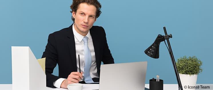 Un homme en costume de bureau est assis à son bureau. Devant lui, un ordinateur portable, un classeur, une lampe de bureau, un pot de crayon, une tasse à café et un pot de plante verte.