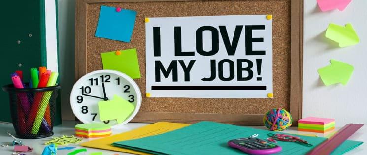 """Sur une table de bureau : un tableau en liège avec une affiche """"I love my job"""", une horloge et des affaires de bureau"""