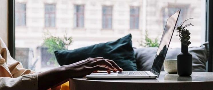 Une paire de main pianote sur un ordinateur portable