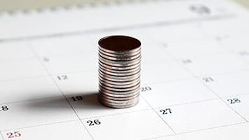Une pile de pièces de monnaie identique sur un calendrier