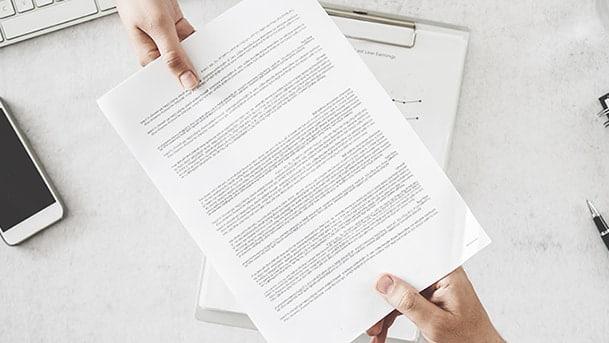 Deux mains de personnes différentes tiennent une page de contrat