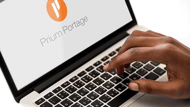Main tapant sur un ordinateur portable avec le logo Prium Portage
