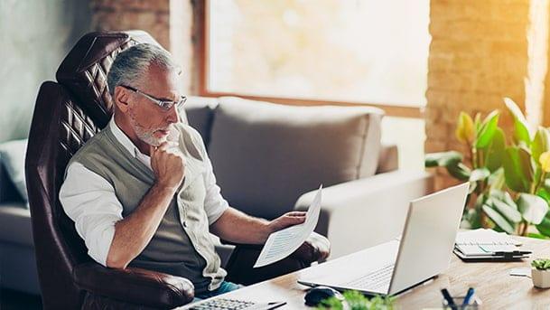 homme barbu assis à son bureau avec ordinateur portable